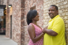 Engagement couple standing against wall portrait session at Brave's stadium
