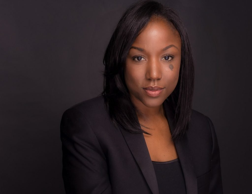 modern studio headshot of black woman in front of grey background